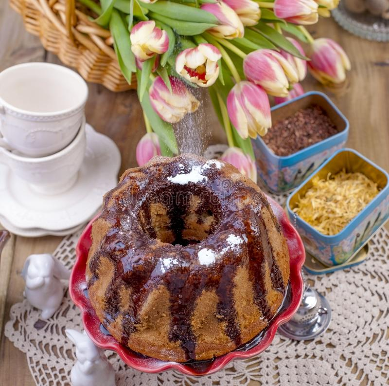 Gâteau doux fait maison, versé avec du chocolat, d'un plat rouge de gâteau Sur un fond en bois, des herbes sèches pour le thé et  image libre de droits