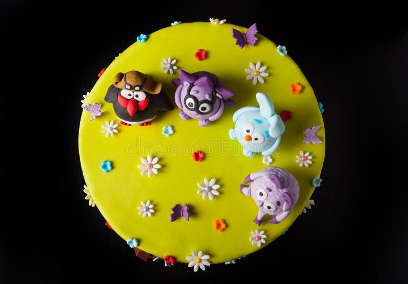Gâteau fait maison avec du mastic pour l'anniversaire du ` s d'enfants sur un CCB noir image stock