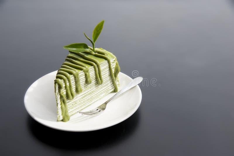 Gâteau japonais de thé vert de Matcha avec des feuilles de thé dans le plat blanc sur la table noire moderne à l'arrière-plan photos libres de droits
