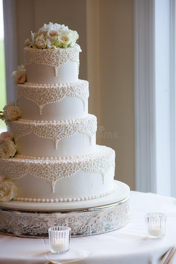Gâteau l'épousant blanc avec les fleurs blanches et conceptions de fantaisie sur une table photo libre de droits