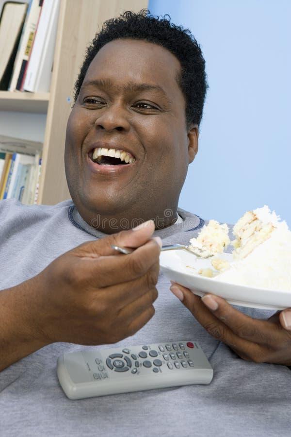 Gâteau Mangeur D Hommes Obèse Photographie stock libre de droits