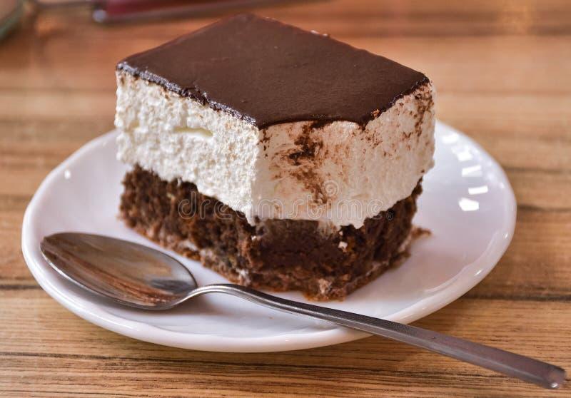 Gâteau mordu d'un plat avec une cuillère photo stock