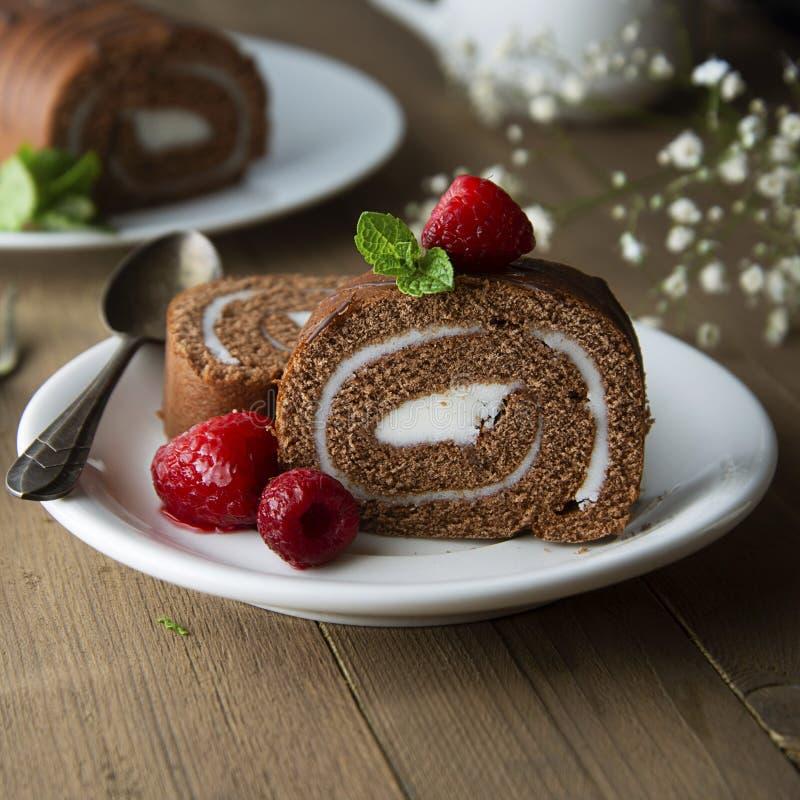 Gâteau mousseline délicieux de petit pain de chocolat avec de la crème de vanille et les feuilles en bon état Nourriture douc photographie stock
