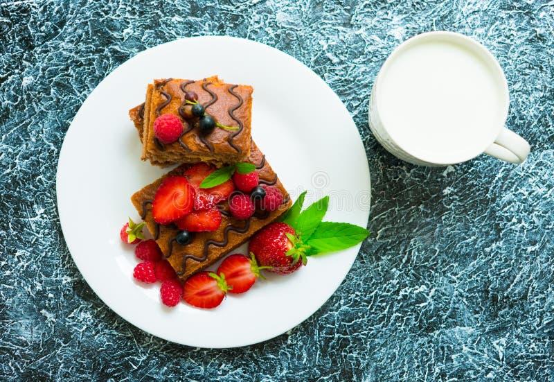 Gâteau mousseline de chocolat avec des baies fraîches et une tasse de lait Dessert d'été sur le fond gris texturisé images stock