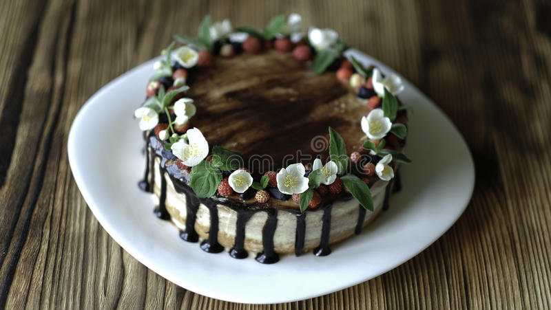 Gâteau nu d'égouttement avec du chocolat, décoré des fraises, des fleurs de jasmin et du chèvrefeuille sur la table en bois brune photographie stock libre de droits