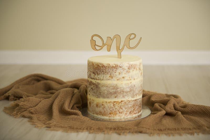 Gâteau nu dans des tons neutres prêts pour un fracas d'un an de gâteau photos stock