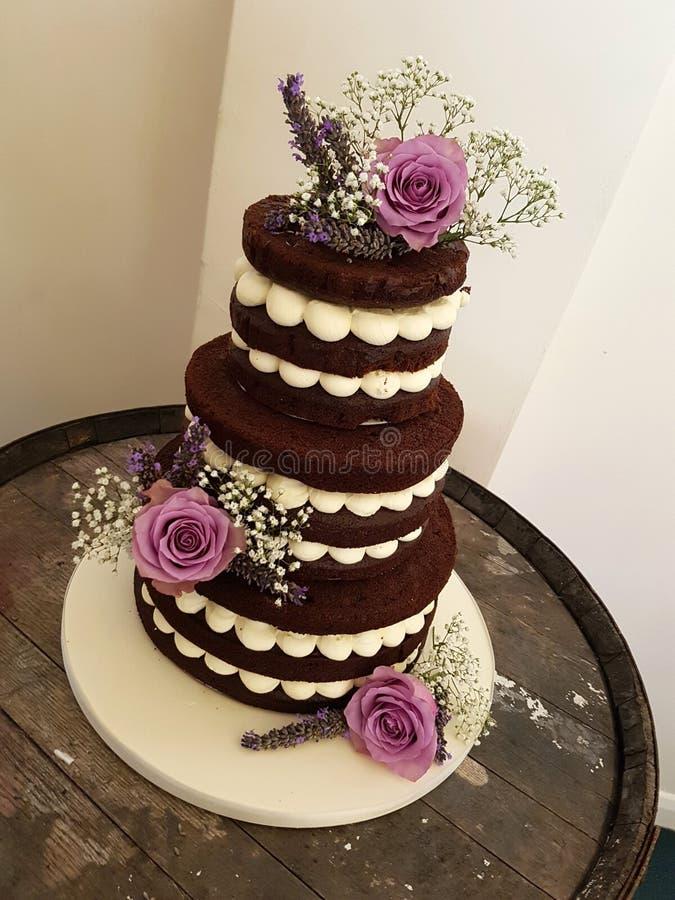 gâteau nu de chocolat de 3 rangées avec les fleurs fraîches images stock