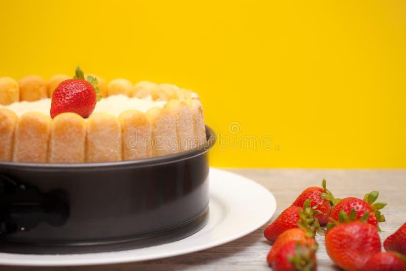 Gâteau ou Charlotte Cake de diplomate avec des strwaberries et des doigts de dame dans la moule sur une table en bois avec le fon photographie stock libre de droits