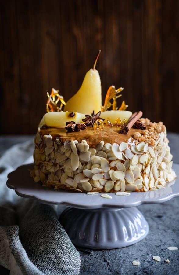 Gâteau posé avec le lustre de caramel, décoré des tranches d'amande, des poires, des décorations de sucre tourné et des bâtons de photographie stock libre de droits