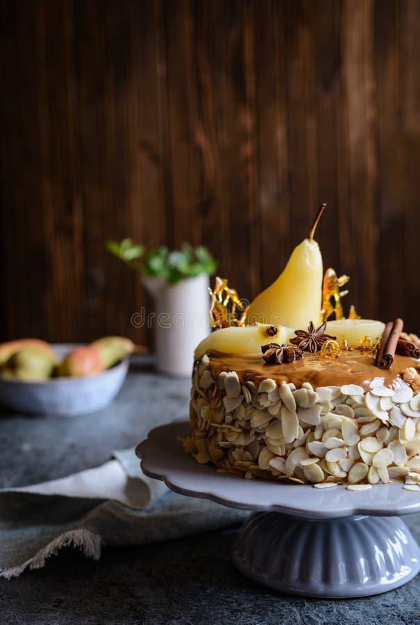 Gâteau posé avec le lustre de caramel, décoré des tranches d'amande, des poires, des décorations de sucre tourné et des bâtons de photos stock