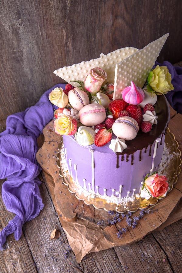 Gâteau pourpre luxueux décoré d'un bise, d'une guimauve, des baies et des fleurs fraîches photo libre de droits