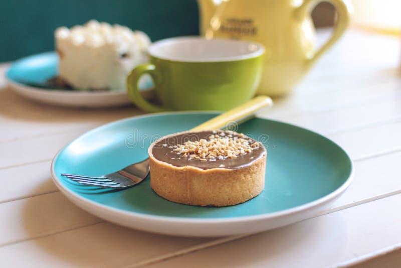 Gâteau rond salé de caramel de plat bleu avec la fourchette, le pot jaune de thé et la tasse verte La tarte délicieuse de chocola photo libre de droits