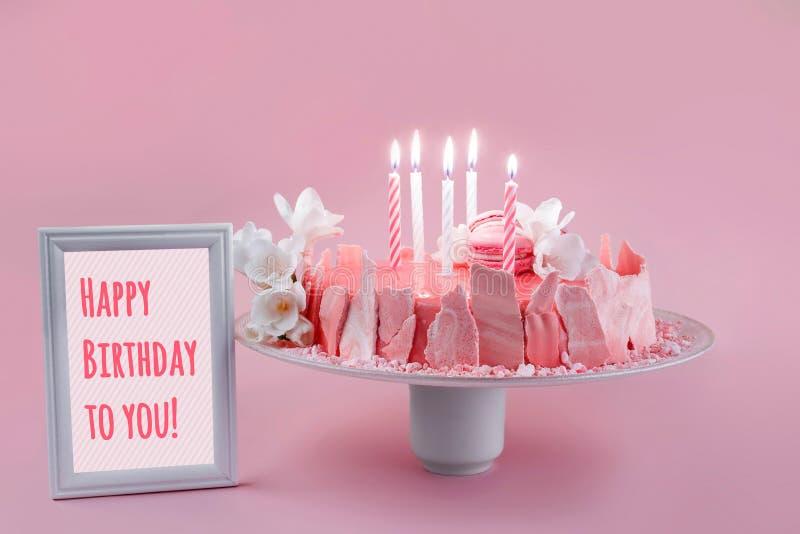 Gâteau rose de mousse avec le lustre de miroir décoré des macarons, des fleurs et du cadre avec le texte pour le joyeux anniversa photos libres de droits