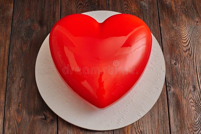 Gâteau rouge de mousse de lustre, forme de forme de coeur sur le fond en bois images stock