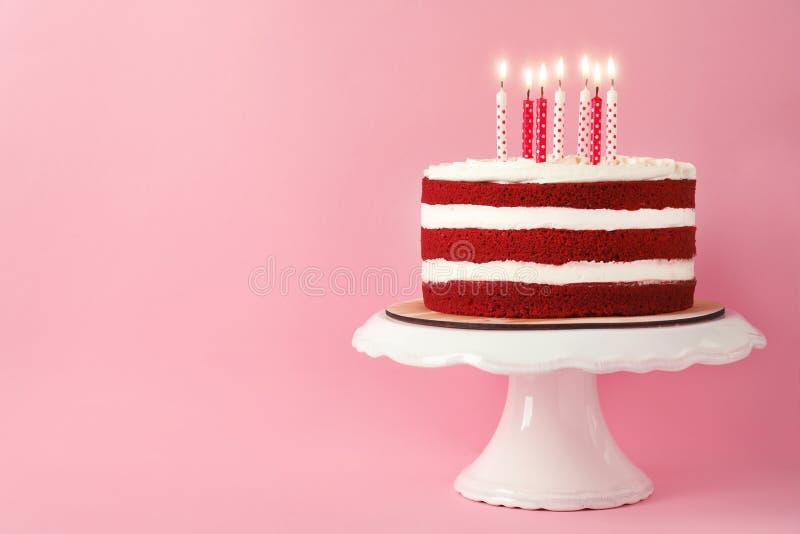 Gâteau rouge fait maison délicieux de velours avec des bougies sur le fond rose photos stock
