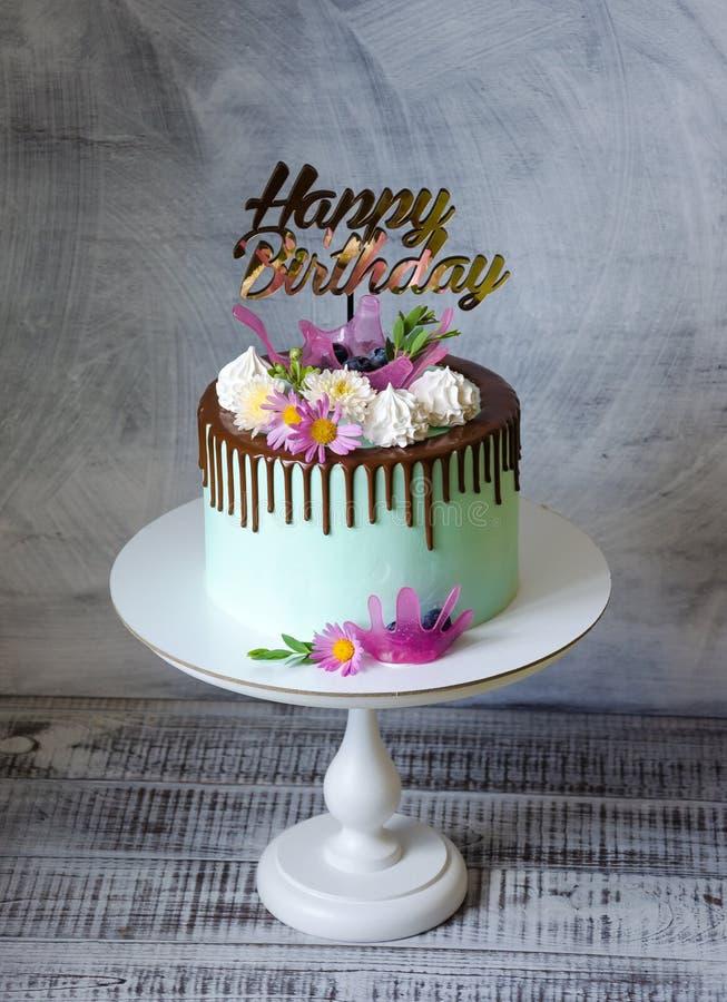 Gâteau savoureux d'égouttement de chocolat décoré du zéphyr et des fleurs photos libres de droits