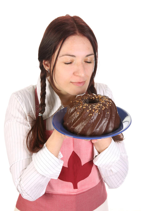 Gâteau sentant de bundt de belle femme au foyer image stock