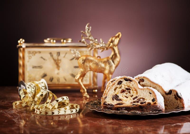 Gâteau Stollen de Noël, cerfs communs d'or et horloge antique image stock