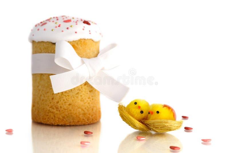 Gâteau traditionnel de Pâques avec deux poussins jaunes et ruban blanc d'isolement sur le fond blanc image libre de droits