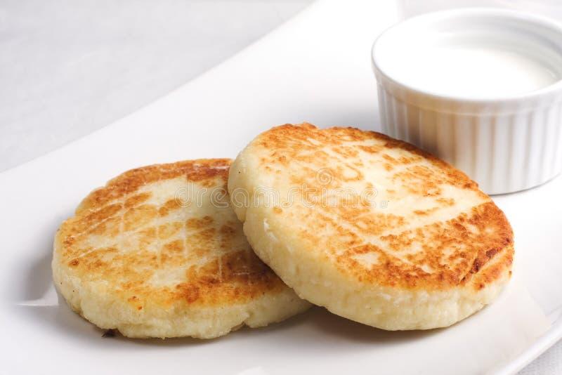Gâteaux au fromage avec la crème sure sur le blanc image stock