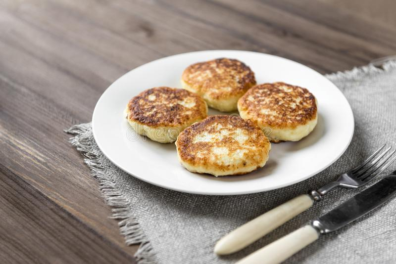 4 gâteaux au fromage d'un plat, 4 beignets de fromage d'un plat blanc, fourchette, couteau sur une serviette sur un fond en bois images libres de droits