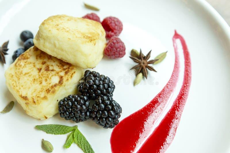 Gâteaux au fromage de lait caillé d'un plat avec des baies Plan rapproché délicieux et sain de petit déjeuner photo libre de droits