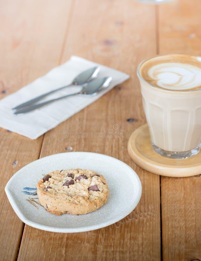 Gâteaux aux pépites de chocolat avec du café dans une tasse en verre image libre de droits