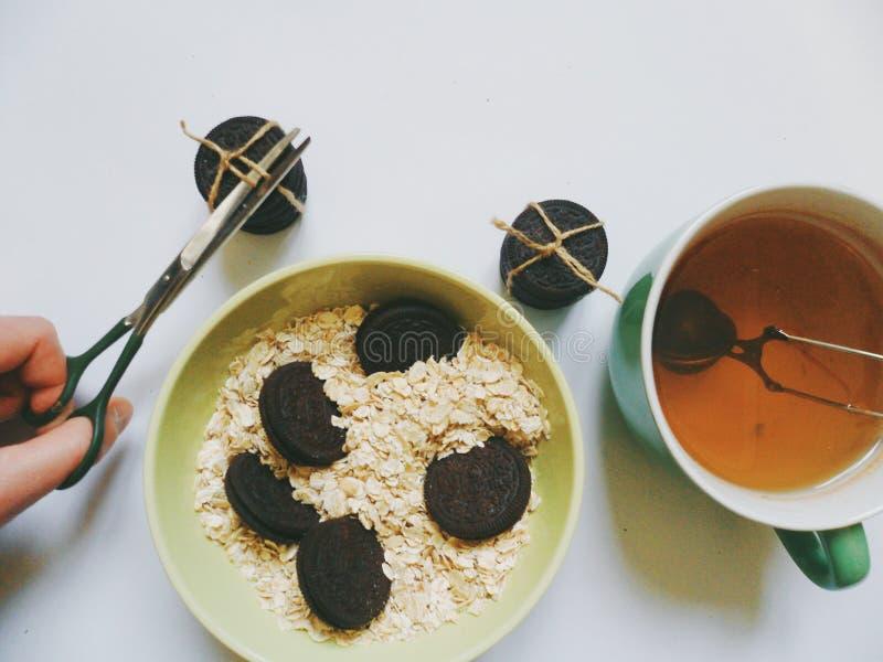 gâteaux aux pépites de chocolat, flocons d'avoine et une tasse de thé vert, mon petit déjeuner photos stock