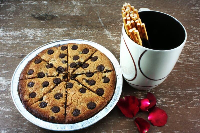 Gâteaux aux pépites de chocolat mous avec des pétales de rose et des bâtons recouverts de chocolat de biscuit image stock