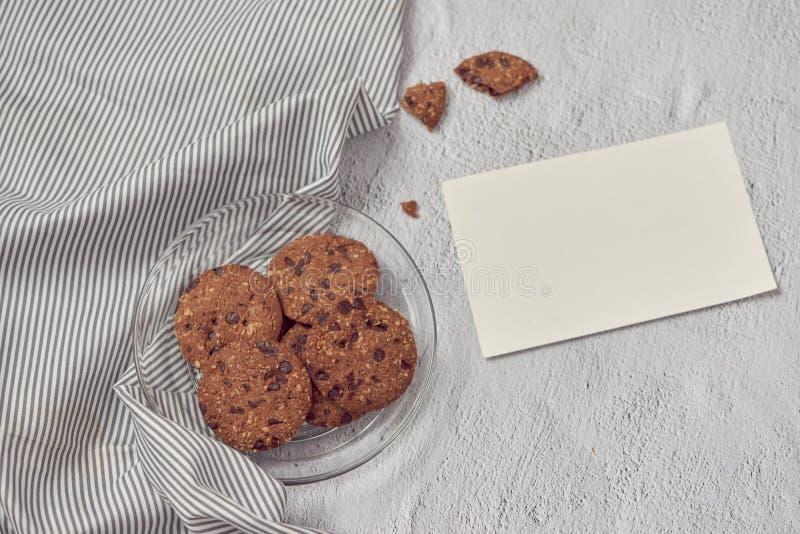 Gâteaux aux pépites de chocolat de plat avec la carte vierge de message sur le blanc photo libre de droits