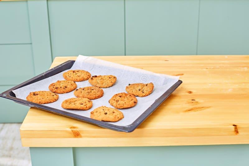 Gâteaux aux pépites de chocolat sur une plaque de cuisson sur une table en bois L'espace pour le texte image libre de droits