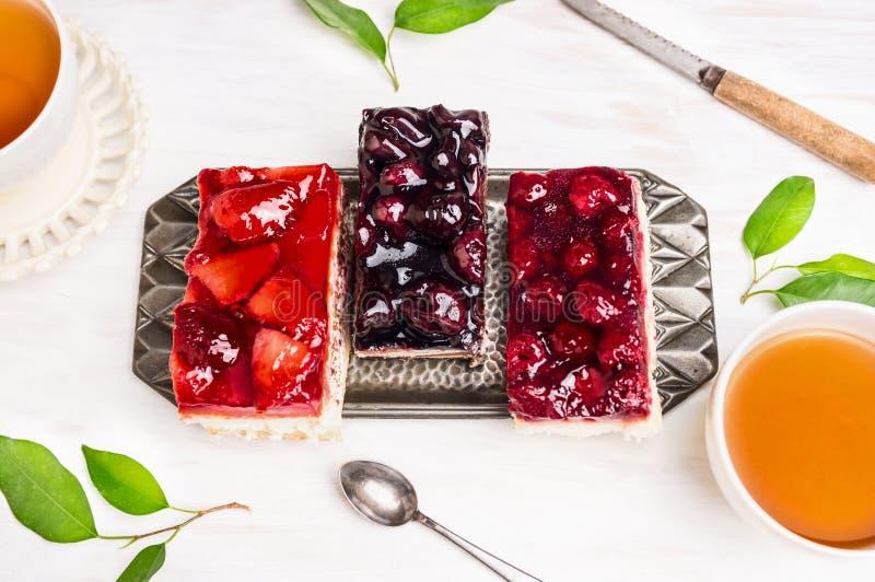 Gâteaux avec des fraises, des cerises, des framboises et des tasses de thé image stock