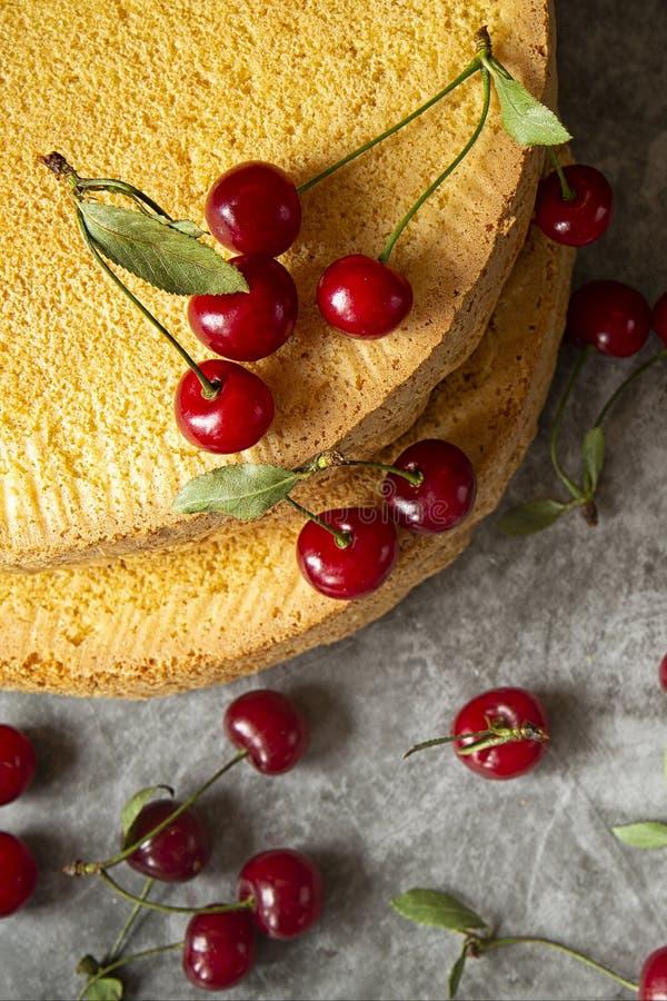 Gâteaux de biscuit avec des baies de cerise sur un fond foncé Cuisson, préparation des couches de l'éponge pour rassembler la cer photo libre de droits