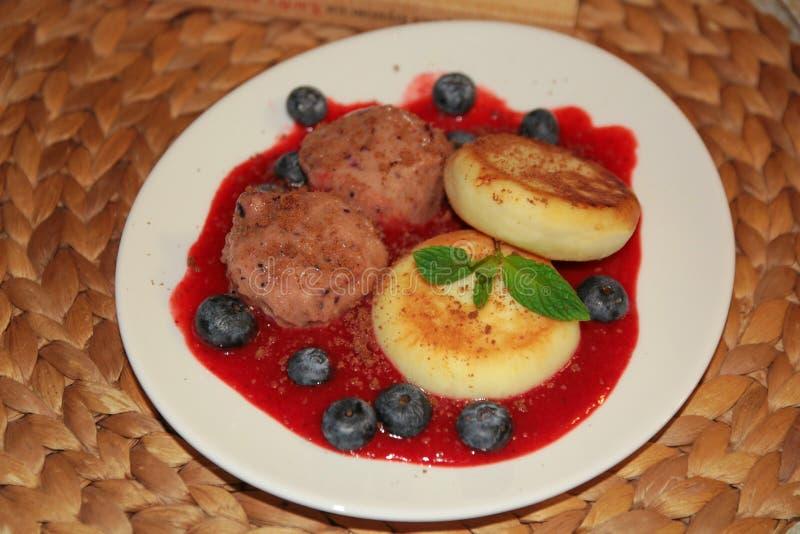 Gâteaux de fromage avec la crème glacée de baie, la sauce à fraise, les myrtilles fraîches et la menthe photos libres de droits