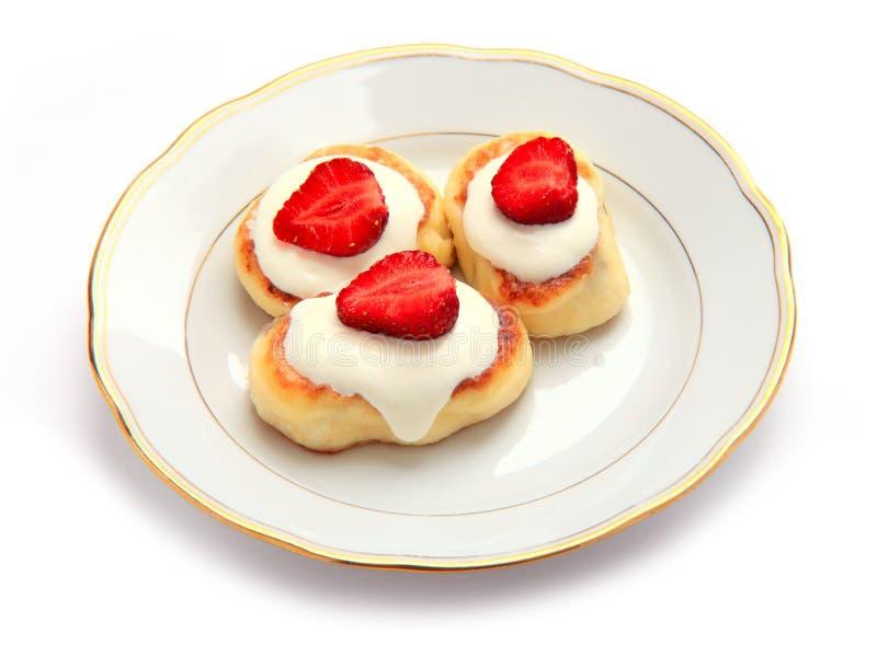 Gâteaux de fromage décorés des fraises de plaque images stock