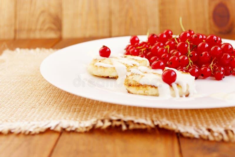 Gâteaux de fromage et baies de groseille rouge fraîche du plat image stock
