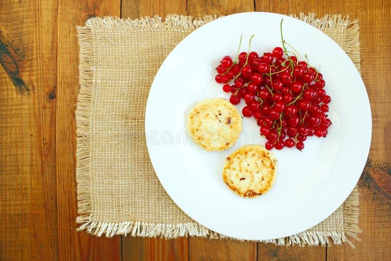 Gâteaux de fromage et baies de groseille rouge fraîche du plat photographie stock libre de droits