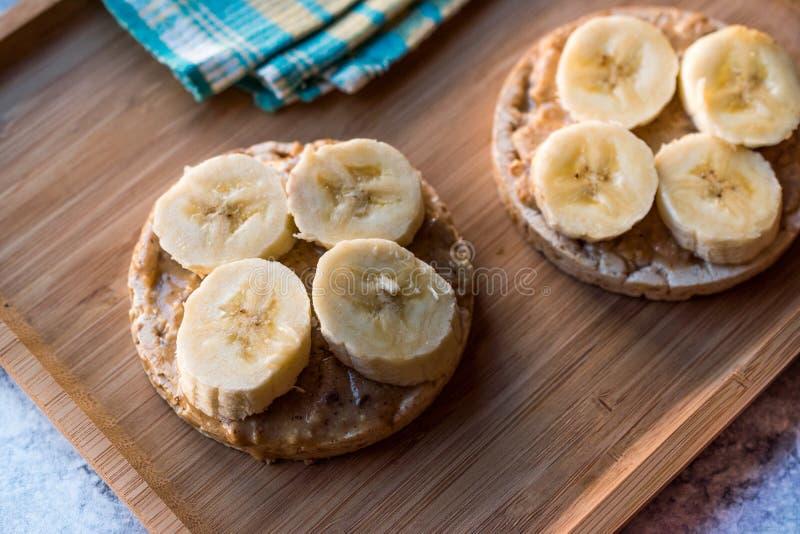 Gâteaux de riz de bulgur avec les bananes et le beurre d'arachide coupé en tranches/biscuits ronds photos stock