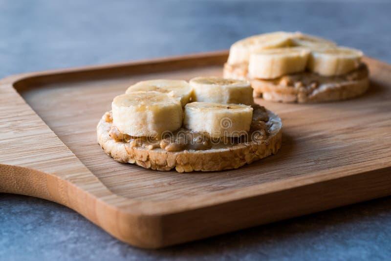 Gâteaux de riz de bulgur avec les bananes et le beurre d'arachide coupé en tranches/biscuits ronds images libres de droits