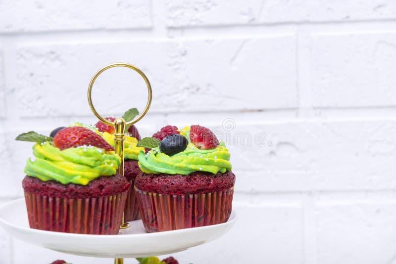 Gâteaux de Savoie avec de la crème, les fraises et les myrtilles vertes sur le mur blanc photo stock