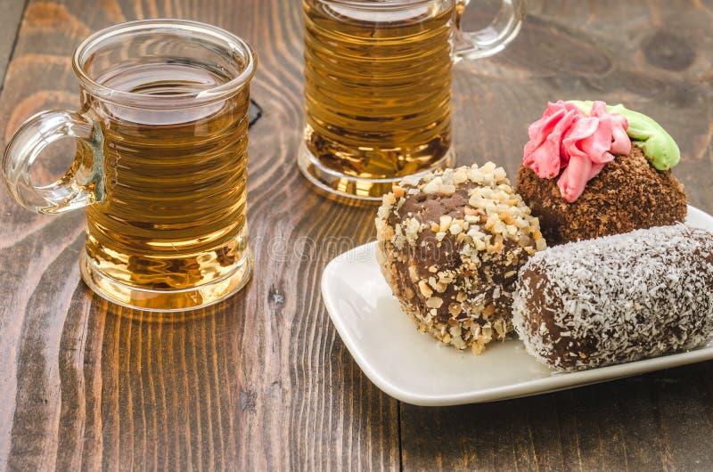 Gâteaux et deux verres de thé/de gâteaux et de deux tasses de thé chaud Foyer s?lectif photographie stock libre de droits