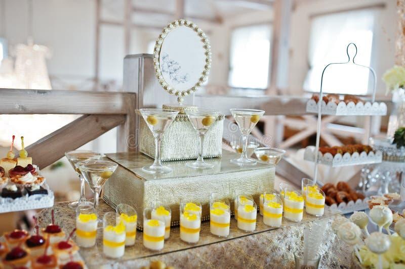 Gâteaux et sucreries de mariage avec des verres d'apéritif à la réception images stock