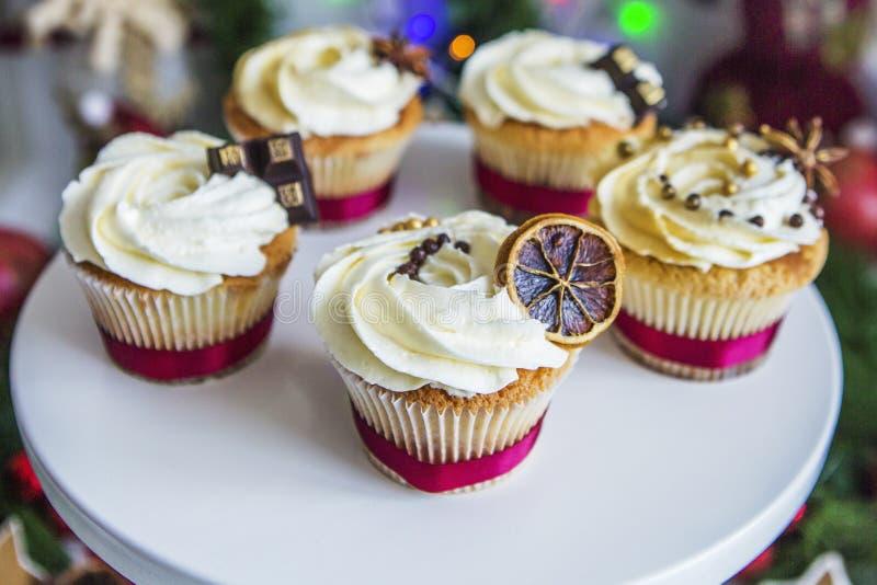 Gâteaux, petits gâteaux avec le citron sec et chocolat sur un piédestal blanc sur un fond de guirlande et de lumières vertes de N image libre de droits