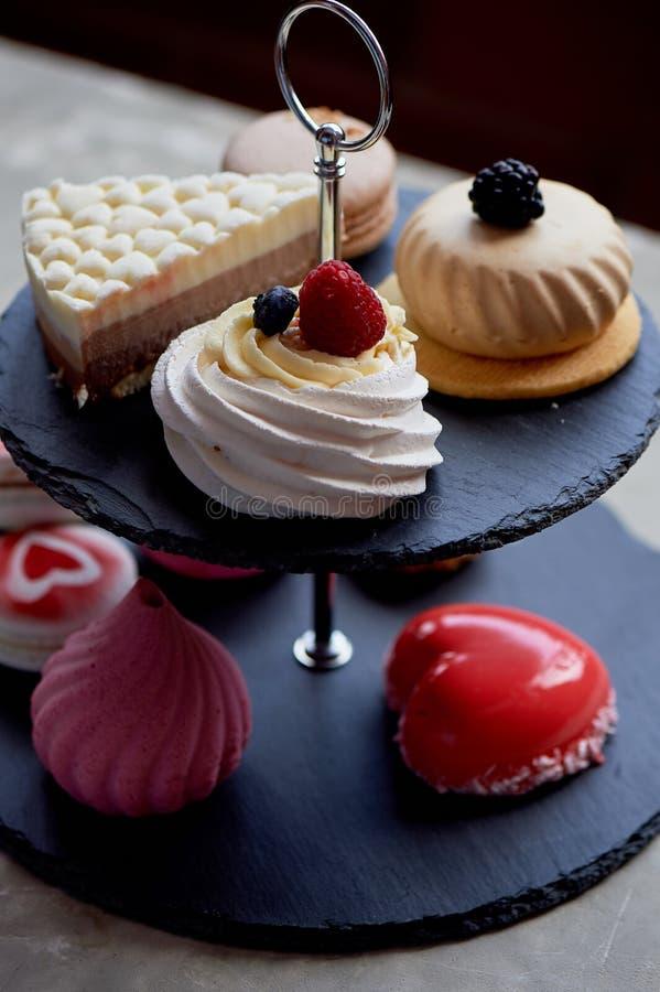 Gâteaux sur un support foncé de couchette d'ardoise desserts Table douce image libre de droits