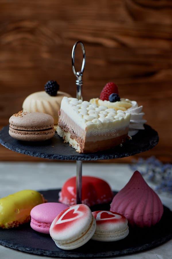 Gâteaux sur un support foncé de couchette d'ardoise desserts Table douce photographie stock libre de droits