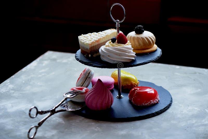 Gâteaux sur un support foncé de couchette d'ardoise desserts Table douce photo libre de droits