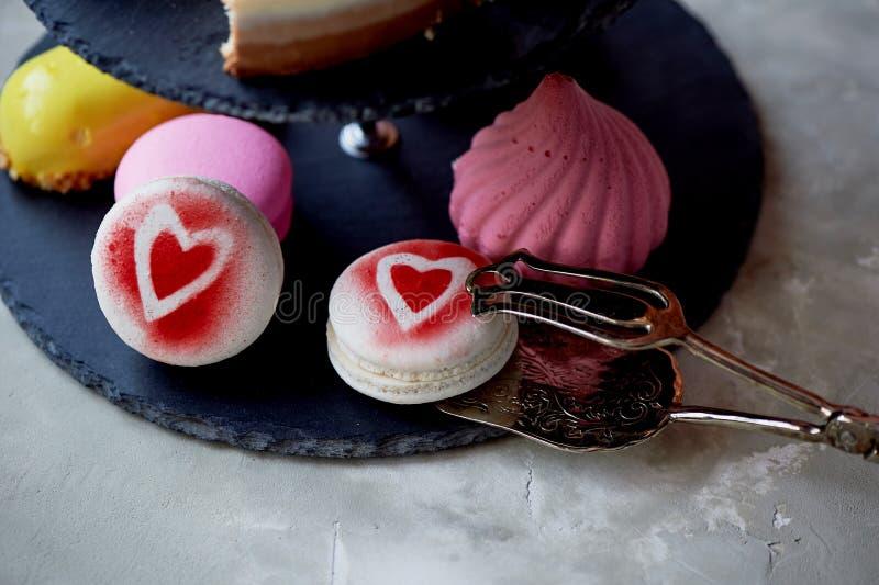 Gâteaux sur un support foncé de couchette d'ardoise desserts Table douce photo stock