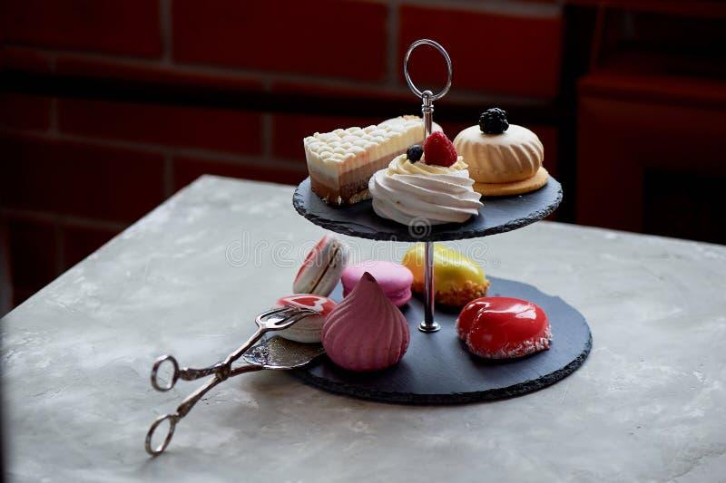 Gâteaux sur un support foncé de couchette d'ardoise desserts Table douce photos stock