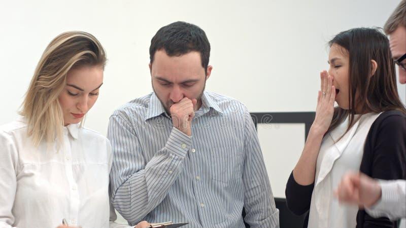 Gähnende Büroangestellte, die nach langer Diskussion müde werden stockfoto