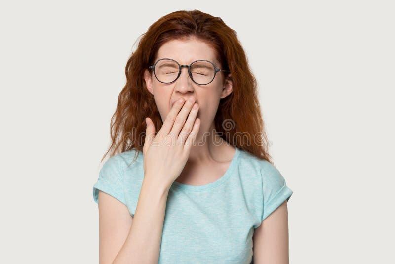 Gähnender Abdeckungsmund der Headshotstudioporträtrothaarigefrau mit der Hand lizenzfreie stockbilder